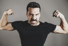 Young handsome man with beard and mustache studio portrait. Showing muscles, fisted hands, power and performance concept Royalty Free Stock Photography