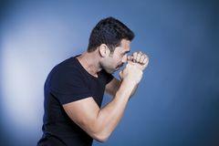 Young handsome man with beard and mustache studio portrait. Fisted hands, boxing concept against blue background royalty free stock photo