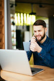 Young handsome man with beard sitting in cafe talking mobile phone, holding cup of coffee and smiling. Laptop on wooden table. Royalty Free Stock Images