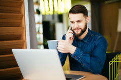 Young handsome man with beard sitting in cafe talking mobile phone, holding cup of coffee and smiling. Laptop on wooden table. Stock Image