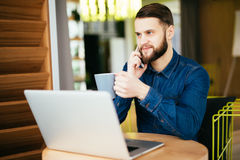Young handsome man with beard sitting in cafe talking mobile phone, holding cup of coffee and smiling. Laptop on wooden table. Stock Photos
