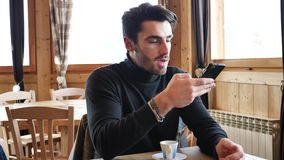 Handsome man using cellphone in cozy ski resort. Young handsome man with beard typing on cell phone, looking outside the window, away confidently on background stock footage