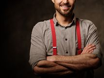 Young handsome man with beard wearing suspenders and posing on dark  background. Royalty Free Stock Photo