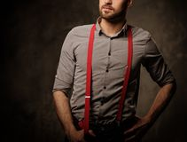 Young handsome man with beard wearing suspenders and posing on dark  background. Stock Image