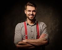 Young handsome man with beard wearing suspenders and posing on dark  background. Royalty Free Stock Images