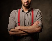 Young handsome man with beard wearing suspenders and posing on dark  background. Royalty Free Stock Image