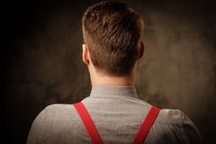 Young handsome man with beard wearing suspenders and posing on dark  background. Stock Images