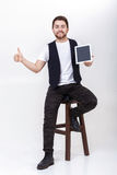 Young handsome man with beard in white shirt and black waistcoat holding tablet and showing thumb up sign on gray. Young handsome brunette man with  beard in Stock Photography