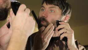 Young Handsome man in beauty saloon working on his beard and styling with comb and hairclipper. stock footage