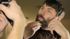 Young Handsome man in beauty saloon working on his beard and styling with comb and hairclipper. stock video
