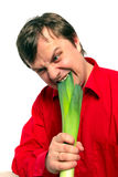 Young handsome man is biting a green leek. Stock Photography