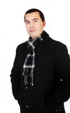 Young handsome man in black coat and scarf isolated. On white Royalty Free Stock Images