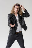 Young handsome man in black leather jacket pointing isolated y. Young handsome man in black leather jacket pointing isolated on grey Stock Image