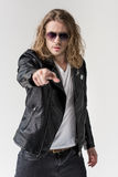 Young handsome man in black leather jacket pointing isolated y. Young handsome man in black leather jacket pointing isolated on grey Royalty Free Stock Image