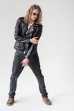Young handsome man in black leather jacket posing isolated. On grey Stock Photography