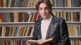 Young handsome man in black leather jacket reading book in library, smiling, portrait of male student studying.  stock video