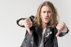 Young handsome man in black leather jacket showing thumbs down isolated. On grey Stock Photography
