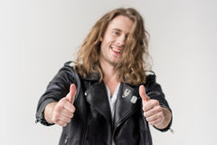 Young handsome man in black leather jacket showing thumbs up isolated. On grey Stock Photography