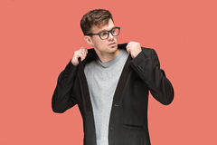 Young handsome man in black suit and glasses isolated on red background Royalty Free Stock Photos