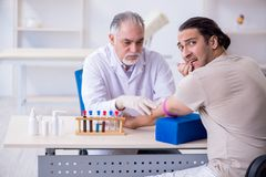 Young handsome man during blood test sampling procedure. The young handsome men during blood test sampling procedure stock image