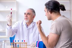 Young handsome man during blood test sampling procedure. The young handsome men during blood test sampling procedure stock photography