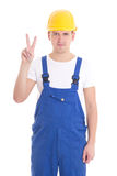 Young handsome man in blue builder uniform showing victory sign. Isolated on white background Stock Photo