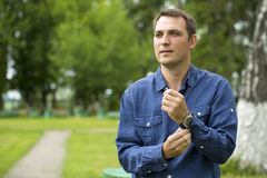Young handsome man in a blue shirt on the background of summer p Stock Images