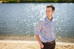 Young man resting near lake. Young handsome man in blue shirt in pattern resting near lake, walking on coast Stock Photo