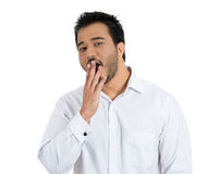 Young handsome man bored of something running out of oxygen to the brain thus yawning Stock Images