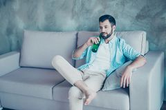 Young handsome man with bristle drinking beer, putting one leg o. N another, relaxing after hard day at home, sitting on the couch, watching his favorite tv royalty free stock image