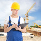 Young handsome man in  builder uniform with clipboard at constru Royalty Free Stock Photo
