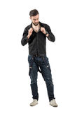 Young handsome man buttoning black shirt. Full body length portrait isolated over white background Stock Photos