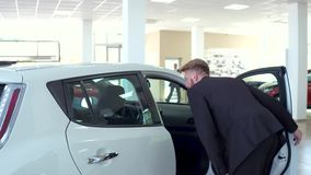 Young handsome man bying car, inspecting interior of the vehicle. stock video footage