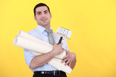 Young handsome man carrying rolls of wallpaper. Against yellow background Royalty Free Stock Photo