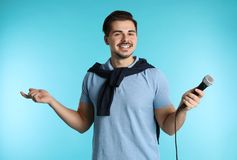 Young handsome man in casual clothes posing with microphone stock photos