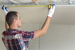 Young handsome man in casual clothing takes measurement of drywall suspended ceiling connected to metal frame on ceiling insulated royalty free stock image