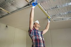 Young handsome man in casual clothing takes measurement of drywall suspended ceiling connected to metal frame on ceiling insulated stock image