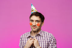 Young handsome man celebrating birthday party over purple background. Royalty Free Stock Photo