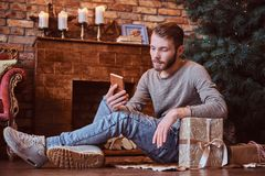 A young handsome man chatting with friends by phone while sitting on a floor surrounded by gifts. Next to the fireplace and Christmas tree stock photography