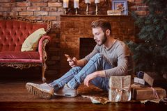 A young handsome man chatting with friends by phone while sitting on a floor surrounded by gifts. Next to the fireplace and Christmas tree royalty free stock photo