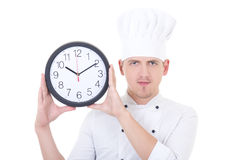 Young handsome man chef in uniform showing office clock isolated Stock Photography