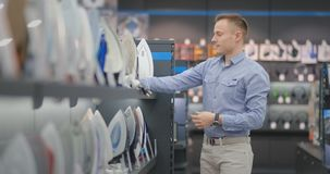 A young handsome man chooses an iron in a consumer electronics store for his new home. Studies the characteristics. Takes samples from the counter and examines stock footage