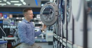 A young handsome man chooses a smart washing machine in a consumer electronics store for his new home. Studies the. Characteristics stock video