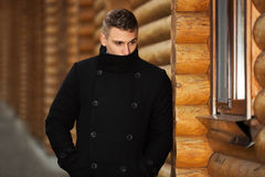 Young handsome man in classic black coat. Standing at the cottage Stock Images