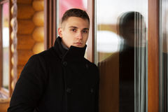 Young handsome man in classic black coat. Standing at the window Royalty Free Stock Images