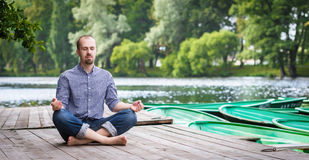 Young handsome man with closed eyes sitting and meditating. Young handsome bearded man with closed eyes sitting on wooden pier, relaxing and meditating in summer stock photo