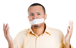 Young handsome man  clueless about his tape covered mouth, irritated Stock Photo