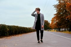Young handsome man in coat. Fashionable well dressed man posing in stylish coat. Confident and focused boy outdoor at autumn. royalty free stock photos