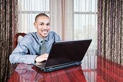 Young Handsome Man at Computer. Close-up of yong, handsome, professional looking Black man dressed in a tie and dress shirt sitting at a table working on a Royalty Free Stock Images