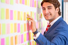 The young handsome man in conflicting priorities concept stock image